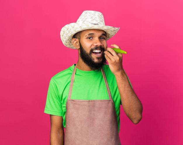 Souriant jeune jardinier afro-américain portant un chapeau de jardinage tenant du poivre montrant un geste de fumer isolé sur un mur rose
