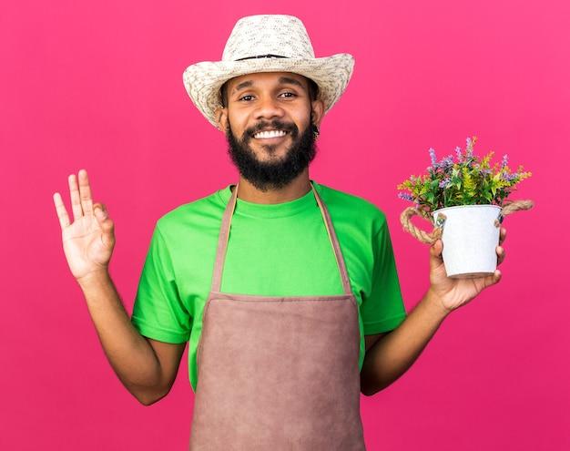 Souriant jeune jardinier afro-américain portant un chapeau de jardinage tenant une fleur dans un pot de fleur montrant un geste correct