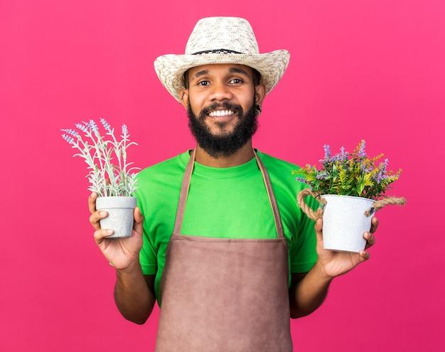 Souriant jeune jardinier afro-américain portant un chapeau de jardinage tenant des fleurs dans un pot de fleurs isolé sur un mur rose