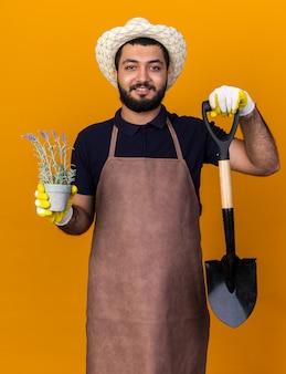 Souriant jeune jardinier mâle caucasien portant chapeau de jardinage et gants tenant pot de fleurs et pelle isolé sur mur orange avec espace copie