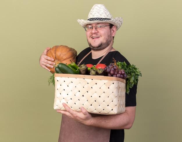 Souriant jeune jardinier mâle portant chapeau de jardinage tenant un panier de légumes avec citrouille isolé sur mur vert olive