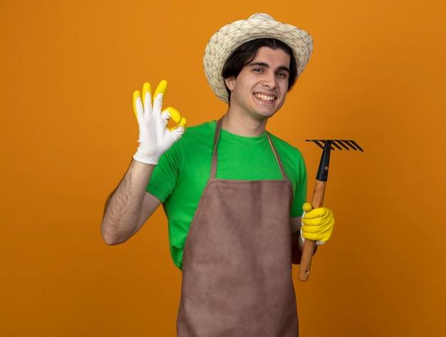 Souriant jeune jardinier mâle en uniforme portant chapeau de jardinage avec des gants tenant râteau montrant bon geste isolé sur orange