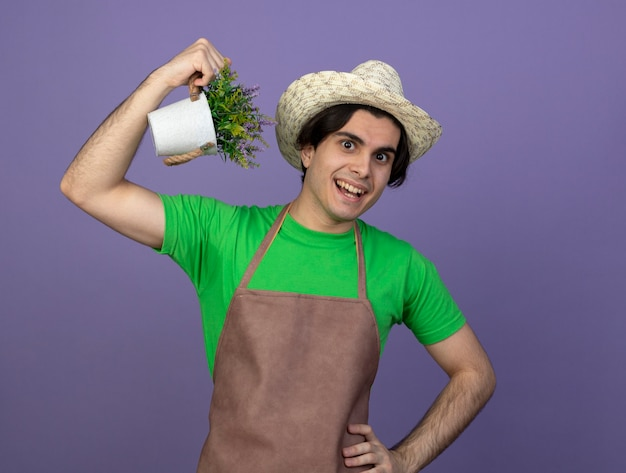 Souriant jeune jardinier mâle en uniforme portant chapeau de jardinage tenant une fleur en pot de fleurs montrant un geste fort mettant la main sur la hanche