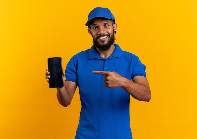 Souriant jeune livreur afro-américain tenant et pointant sur un téléphone isolé sur un mur orange avec espace de copie