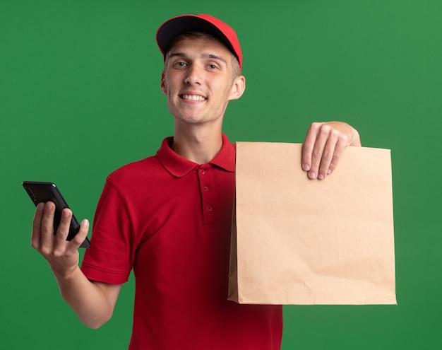 Souriant jeune livreur blonde détient un paquet de papier et téléphone sur vert