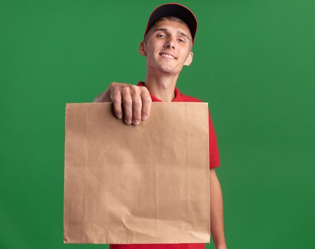 Souriant jeune livreur blonde détient un paquet de papier sur vert