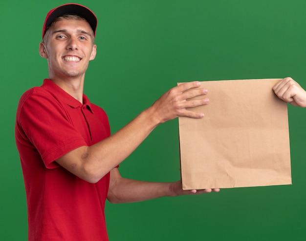 Souriant jeune livreur blonde donne un paquet de papier à quelqu'un et regarde la caméra sur le vert