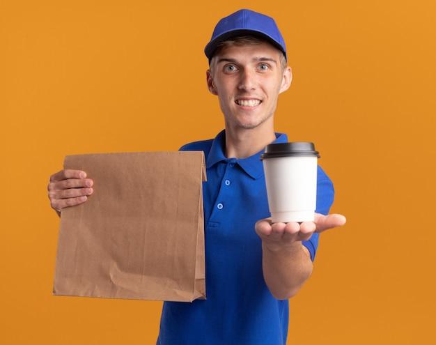 Souriant jeune livreur blonde tenant un paquet de papier et une tasse sur orange