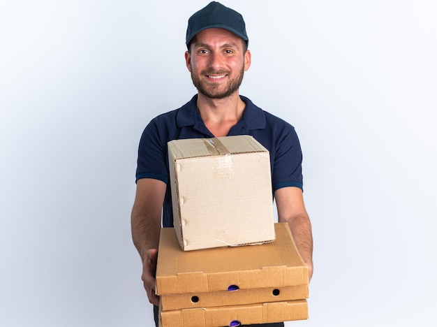 Souriant jeune livreur caucasien en uniforme bleu et casquette étirant les paquets de pizza et la boîte en carton vers la caméra