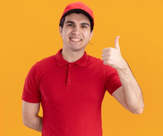 Souriant jeune livreur caucasien en uniforme bleu et casquette gardant la main derrière le dos montrant le pouce vers le haut