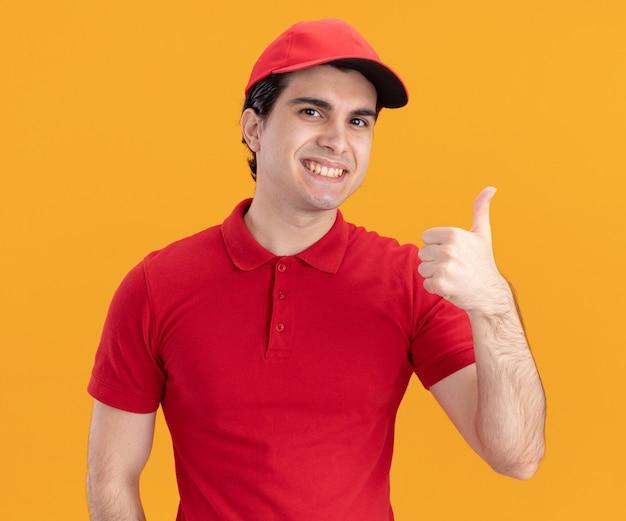 Souriant jeune livreur caucasien en uniforme bleu et casquette montrant le pouce vers le haut