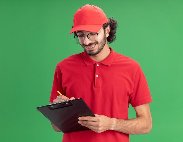 Souriant jeune livreur caucasien en uniforme rouge et casquette portant des lunettes écrivant sur le presse-papiers avec un crayon