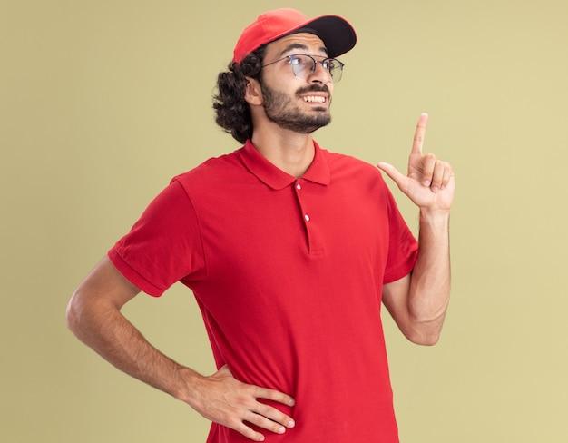 Souriant jeune livreur caucasien en uniforme rouge et casquette portant des lunettes en gardant la main sur la taille en regardant le côté pointant vers le haut