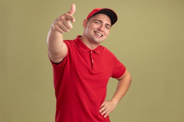 Souriant jeune livreur portant l'uniforme et une casquette vous montrant le geste et mettant la main sur la hanche isolé sur mur vert olive