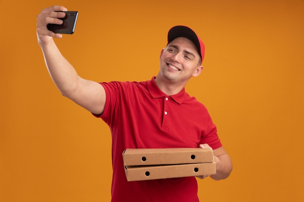 Souriant jeune livreur en uniforme avec capuchon tenant des boîtes de pizza prendre un selfie isolé sur un mur orange