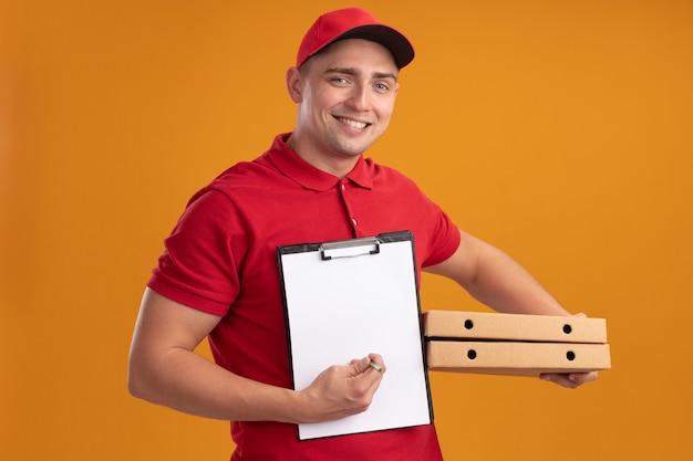 Souriant jeune livreur en uniforme avec capuchon tenant des boîtes de pizza avec presse-papiers isolé sur mur orange