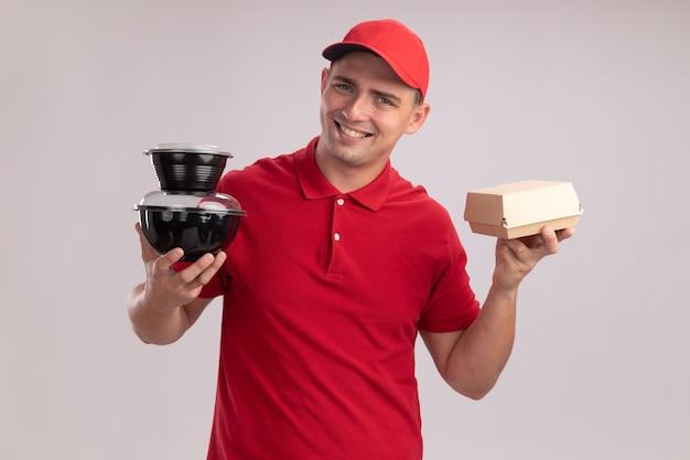 Souriant jeune livreur en uniforme avec capuchon tenant des contenants de nourriture avec du papier d'emballage alimentaire isolé sur mur blanc