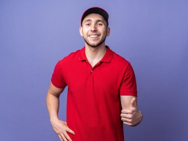 Souriant jeune livreur en uniforme avec casquette montrant le pouce vers le haut mettant la main sur la hanche
