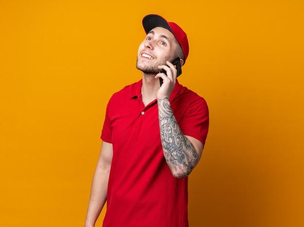 Souriant jeune livreur en uniforme avec casquette parle au téléphone