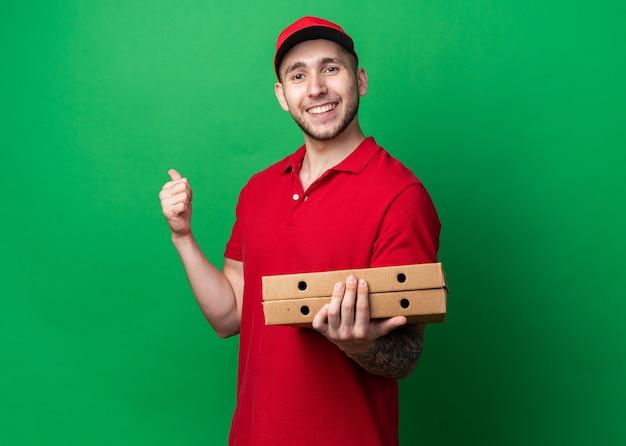 Souriant jeune livreur en uniforme avec casquette tenant des boîtes à pizza montrant le pouce vers le haut