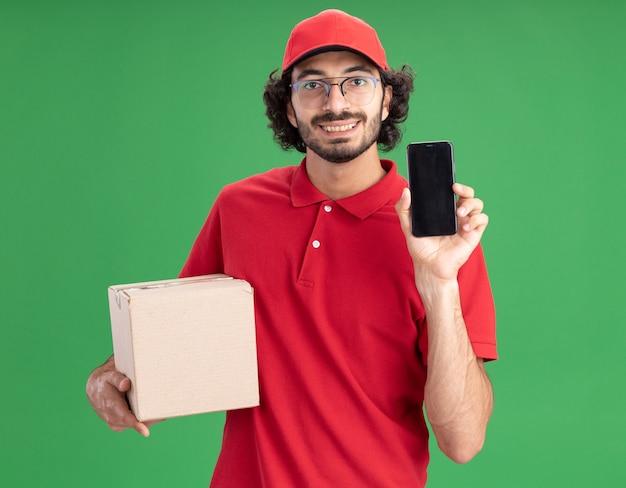 Souriant jeune livreur en uniforme rouge et casquette portant des lunettes tenant une boîte à cartes montrant un téléphone portable à l'avant en regardant l'avant isolé sur un mur vert