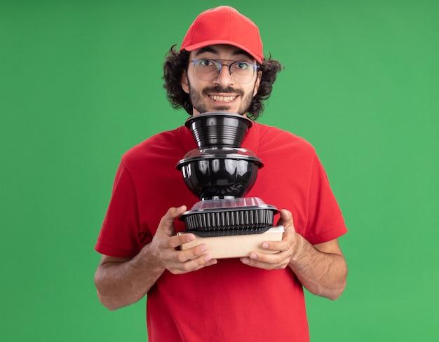 Souriant jeune livreur en uniforme rouge et casquette portant des lunettes tenant un emballage alimentaire en papier et des récipients alimentaires sous le menton regardant l'avant isolé sur un mur vert