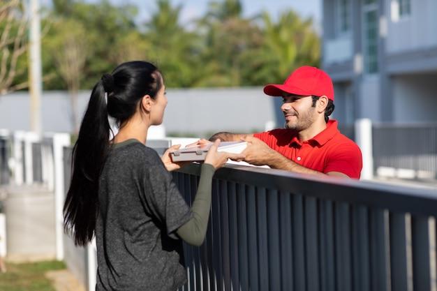 Souriant jeune livreur en uniforme rouge tenant une boîte donne à la belle femme costumière devant la maison.
