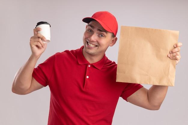 Souriant jeune livreur vêtu d'un uniforme avec capuchon tenant un paquet de nourriture en papier avec une tasse de café isolé sur un mur blanc