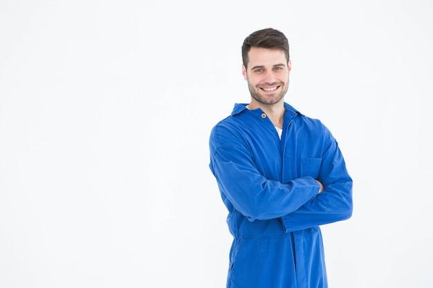 Souriant jeune mâle debout bras croisés