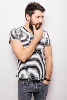 Souriant jeune mannequin barbu habillé avec désinvolture, isolé sur un mur blanc.