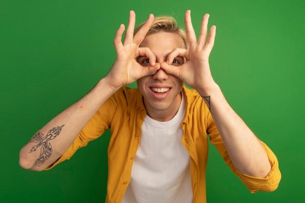 Souriant jeune mec blond portant un t-shirt jaune montrant le geste de regard isolé sur vert