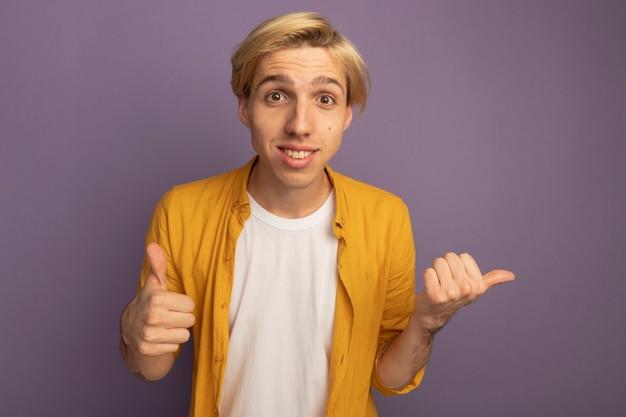 Souriant jeune mec blond portant un t-shirt jaune montrant le pouce vers le haut isolé sur violet