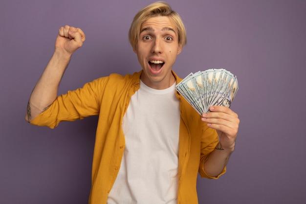 Souriant jeune mec blond portant un t-shirt jaune tenant de l'argent et montrant oui geste isolé sur violet