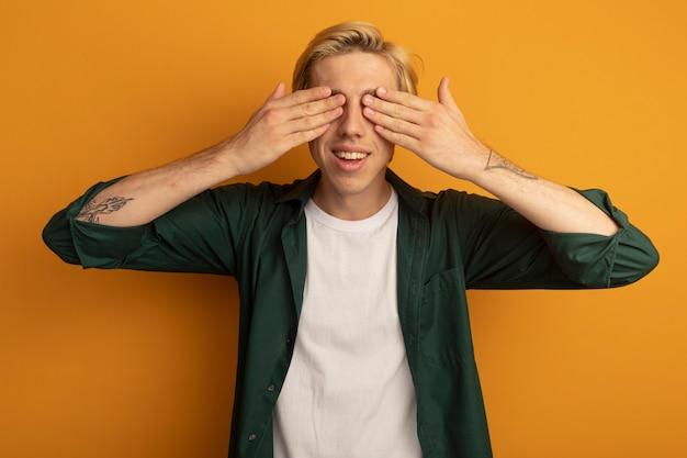 Souriant jeune mec blond portant un t-shirt vert couvert les yeux avec les mains