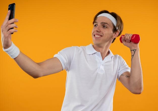 Souriant jeune mec sportif portant bandeau et bracelet exercice avec haltère et prendre un selfie isolé sur un mur orange