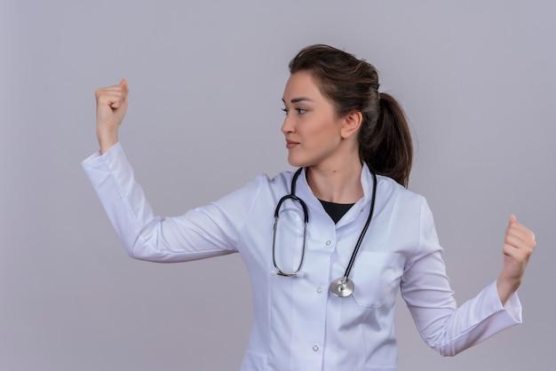 Souriant jeune médecin portant une blouse médicale portant le poing levé stéthoscope sur mur blanc