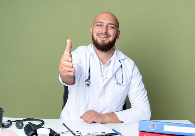 Souriant jeune médecin de sexe masculin chauve portant une robe médicale et un stéthoscope assis au travail de bureau
