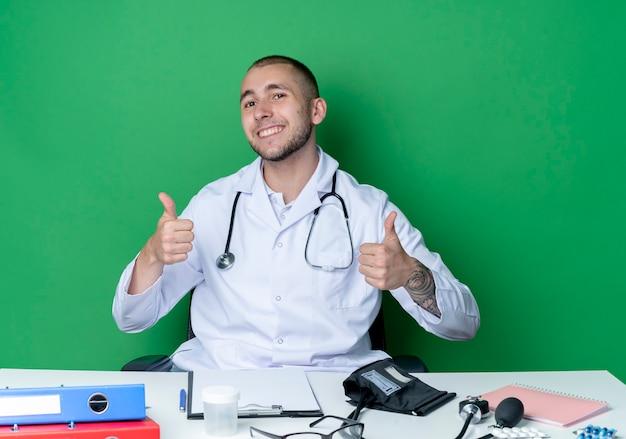 Souriant jeune médecin de sexe masculin portant une robe médicale et un stéthoscope assis au bureau avec des outils de travail montrant les pouces vers le haut isolé sur le mur vert