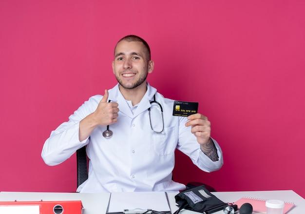 Souriant jeune médecin de sexe masculin portant une robe médicale et un stéthoscope assis au bureau avec des outils de travail tenant une carte de crédit et montrant le pouce vers le haut isolé sur un mur rose
