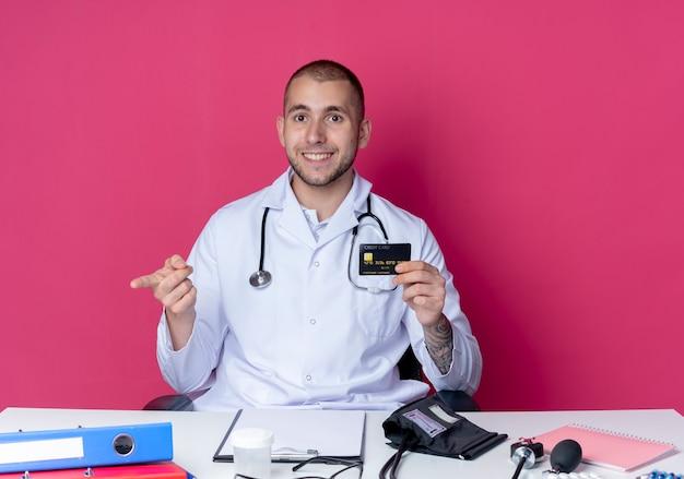 Souriant jeune médecin de sexe masculin portant une robe médicale et un stéthoscope assis au bureau avec des outils de travail tenant une carte de crédit pointant tout droit isolé sur un mur rose