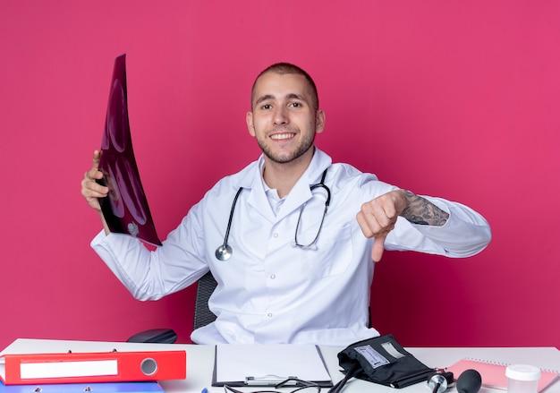 Souriant jeune médecin de sexe masculin portant une robe médicale et un stéthoscope assis au bureau avec des outils de travail tenant des rayons x et pointant vers le bas isolé sur un mur rose