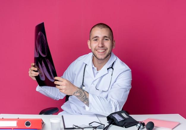 Souriant jeune médecin de sexe masculin portant une robe médicale et un stéthoscope assis au bureau avec des outils de travail tenant un tir aux rayons x isolé sur un mur rose