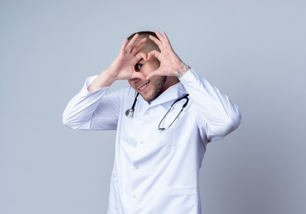 Souriant jeune médecin de sexe masculin portant une robe médicale et un stéthoscope autour de son cou faisant signe de coeur et regardant à l'avant à travers il isolé sur mur blanc