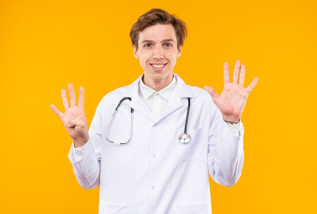 Souriant jeune médecin de sexe masculin portant une robe médicale avec un stéthoscope montrant différents numéros isolés sur un mur orange
