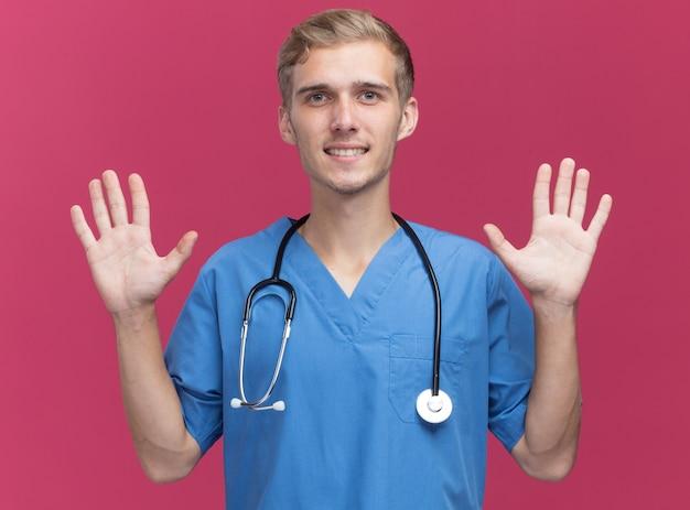 Souriant jeune médecin de sexe masculin portant l'uniforme de médecin avec stéthoscope levant les mains isolé sur mur rose