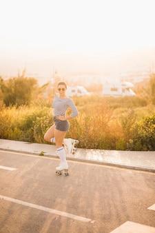 Souriant jeune patineuse debout sur une jambe posant sur la route