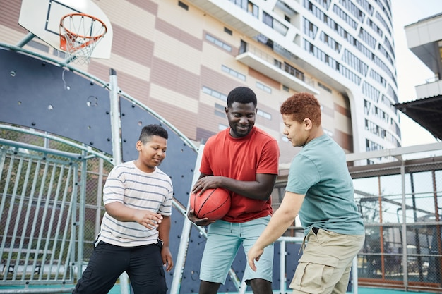 Souriant jeune père jouant au basket-ball avec ses fils et leur cachant le ballon sur le terrain de sport de la ville
