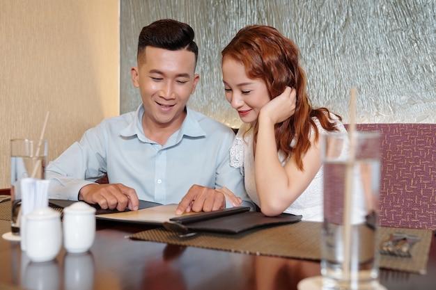 Souriant jeune petit ami et petite amie assis à la table du restaurant et lisant le menu avant de commander de la nourriture