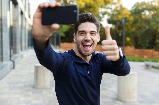 Souriant jeune sportif prenant un selfie assis à l'extérieur, posant, pouces vers le haut