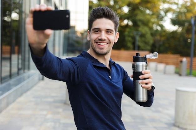 Souriant jeune sportif prenant un selfie assis à l'extérieur, posant, tenant une bouteille d'eau